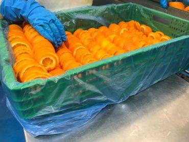 Caja de plastico verde con naranjas cortadas dentro
