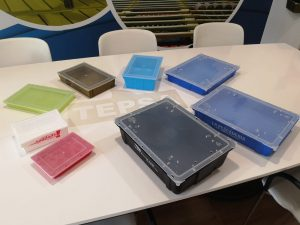 plastic crates in different colours over a white table